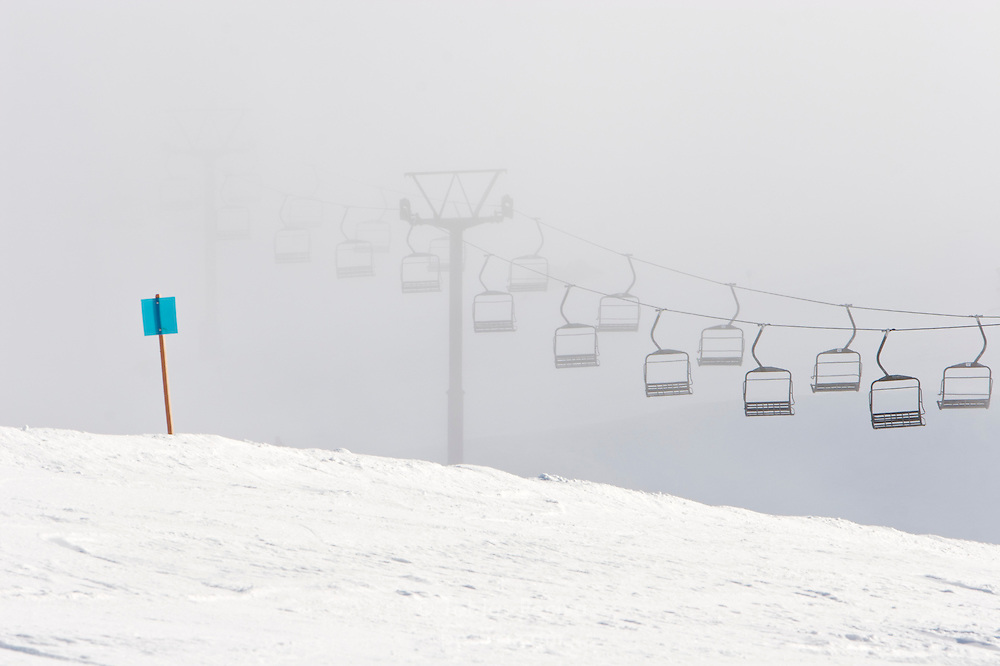 An idle chairlift emerges from low cloud cover at ski field Turoa. Turoa is located on active volcano Mount Ruapehu, New Zealand.