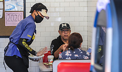 Waffle House's Miss D (left) serves Daniel Bahena and his guest (right) on Monday, April 27, 2020 at The Waffle House in Brookhaven, Ga. Restaurants around metro Atlanta began to reopen dining rooms Monday, April 27, 2020 as restrictions related to the coronavirus pandemic are lifted. Restaurants will be allowed to operate with in-person dining as long as they follow a set of 39 guidelines laid out by the state government, which include a requirement that all employees wear masks, a maximum of 10 customers per 500 square feet of floor space and a maximum of six diners per table. Photo by John Spink/Atlanta Journal-Constitution/TNS/ABACAPRESS.COM