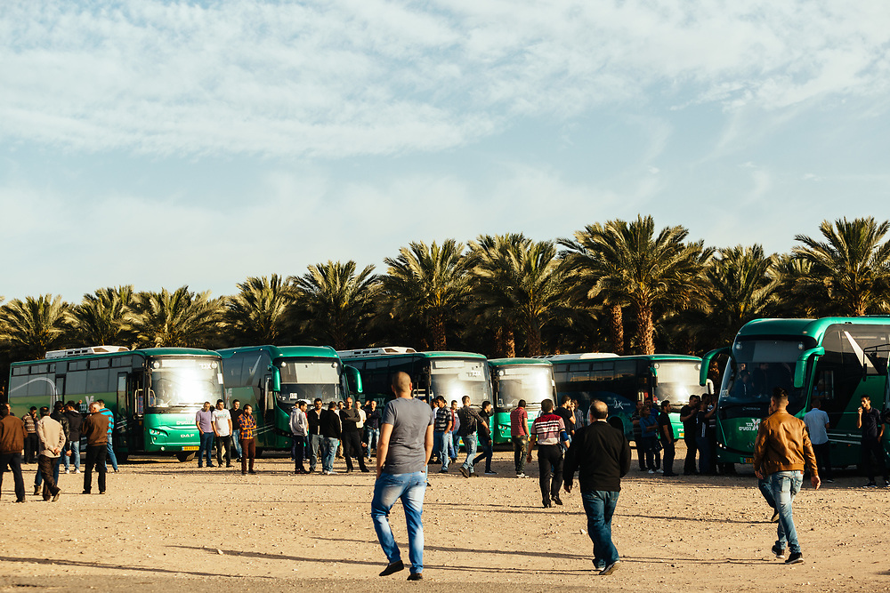 Jordanian workers wait outside the Yitzhak Rabin Border Terminal for the departure of buses transporting them to various hotels where they work in Eilat, southern Israel, after crossing the border from Jordan into Israel, on March 15, 2018.