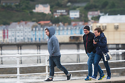 © Licensed to London News Pictures. 21/09/2018. Aberystwyth, UK. People walking in Aberystwyth feel the gale force winds of Storm Bronagh, the second named storm of the UK winter.Photo credit: Keith Morris/LNP