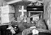 Inside tomb in the public cemetery in Navotas Manila, the belongings of another family, to the cross of Christ serves to pose a photograph of family.