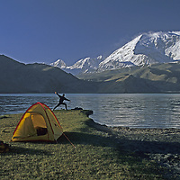 CHINA, Xinjiang Province.  Mark Newcomb<br /> (MR) stretches in camp by Lake Karakul in Pamir Mts.  24,750' Mt. Mustagh Ata bkg.