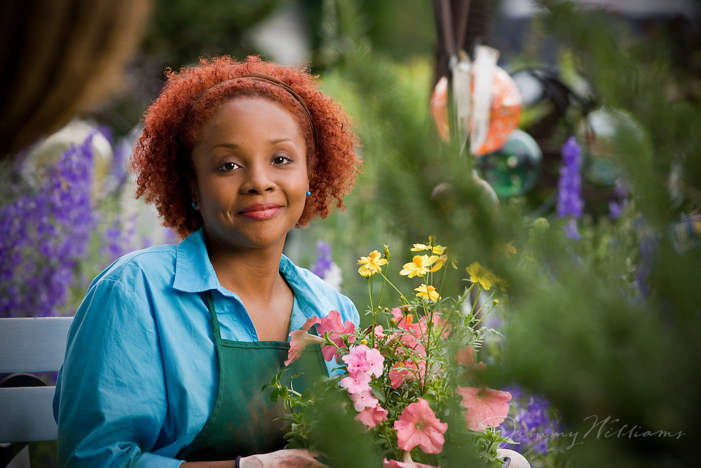 An african-american woman sits in her garden, holding a plant.