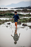 """Boy with long rubber boots walking on the slowly closing """"Mysterious Sea Road"""" at Hoedong shore (Jindo island). Jindo is the 3rd biggest island in South Korea located in the South-West end of the country and famous for the """"Mysterious Sea Route"""" or """"Moses Miracle"""". Every spring thousands flock to the shores of Jindo to walk the mysterious route that stretches roughly three kilometers from Hoedong to the distant island of Modo. Materializing from the rise and fall of the tides, the divide can reach as wide as forty meters."""