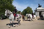 Military personel on horseback ride past Wellington Arch through Hyde Park Corner in London, England, United Kingdom.