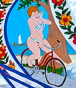 Painting of a woman wearing a bikini riding a bicycle near the ocean. Traditional boat decoration from Portugal