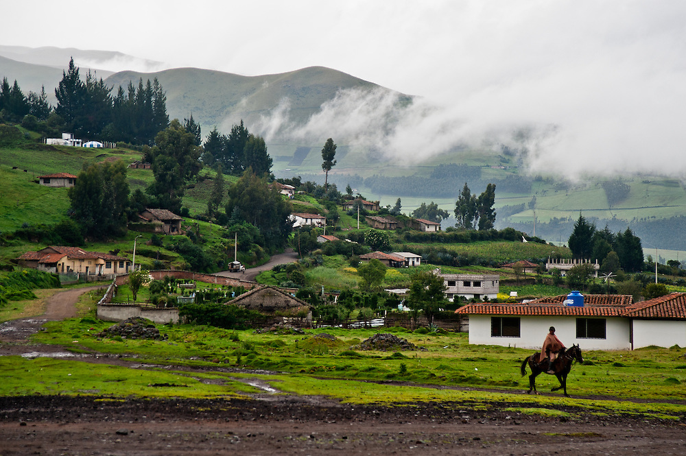 A dairy farmer on horseback brings milk to a quality testing location in the Andes of Ecuador.
