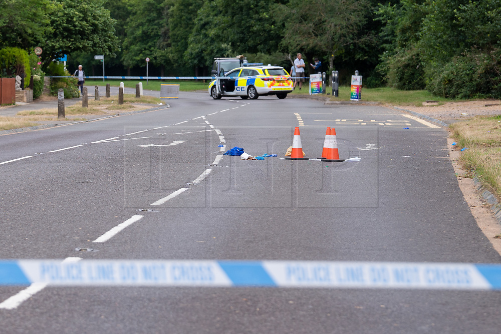 © Licensed to London News Pictures. 27/07/2021. Stoke Poges, UK. A police vehcile and police tape form a cordon at the scene on Bells Hill in Stoke Poges, Buckinghamshire, following an assault on Monday 26 July at approximately 21:30BST. A man in his twenties suffered a serious leg injury following the assault which is understood to have involved a machete. Two men, aged 19 and 21, and a 20-year-old woman have been arrested on suspicion of section 18 wounding with intent. Photo credit: Peter Manning/LNP