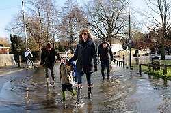 © Licensed to London News Pictures. 19/01/2014. A woman and her children walk through flood water. The town of Eynsford in Kent flooded where the river Darent has broken it's banks after overnight rain caused river levels to rise. Photo credit :Grant Falvey/LNP