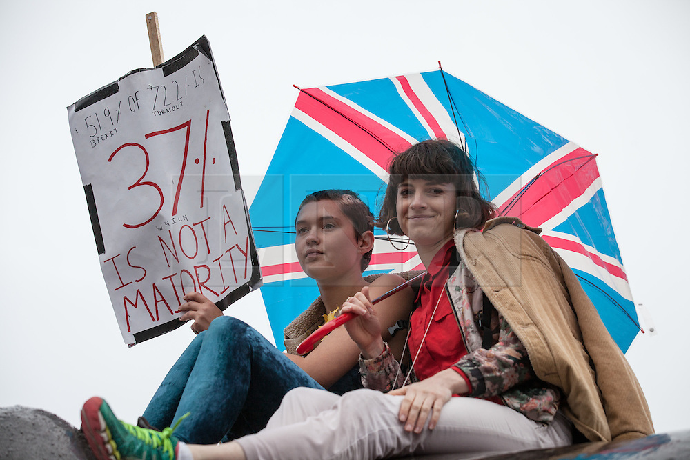 © Licensed to London News Pictures. 28/06/2016. London, UK. Two girls sit on top of one of Trafalgar Square's famous lions at an anti-Brexit protest. On Thursday 23 June, Britain voted to leave the European Union in a historic referendum. Photo credit: Rob Pinney/LNP