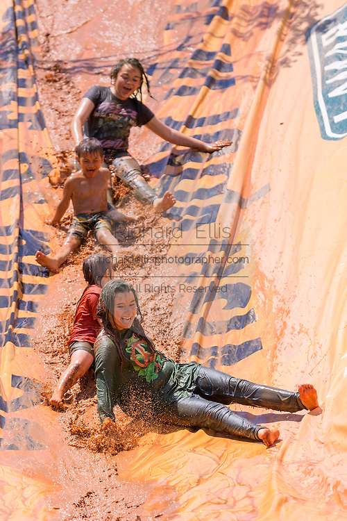 A group slips down a mud slide during the 2015 National Red Neck Championships May 2, 2015 in Augusta, Georgia. Hundreds of people joined in a day of country sport and activities.