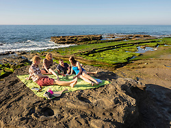Group of young friends picnicking on rocky beach at Playa de Azkorri, Getxo, Basque Country, Spain