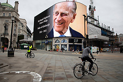 © Licensed to London News Pictures.10/04/2021. London, UK. A tribute to Prince Philip is displayed on a large screen in Piccadilly Circus. Yesterday Buckingham Palace announced that Prince Philip The Duke of Edinburgh passed away in the morning at Windsor Castle . Photo credit: George Cracknell Wright/LNP