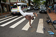 A Capoeirista demonstrate his art for money on the streets of Rio de Janeiro, Brazil. Capoeira is a mixture of martial arts, games, and dance that originated in Brazil created and developed by African slaves during the 16th century. Participants form a roda circle and take turns playing instruments, singing, and sparring in pairs. Enormously acrobatic, Capoeira was for most of its existence banned by the Brazilian authorities. It is now seen as a national sport.
