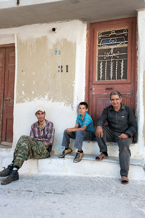 Men sitting outside a house in the medieval village of Pyrgi in Chios Greece.