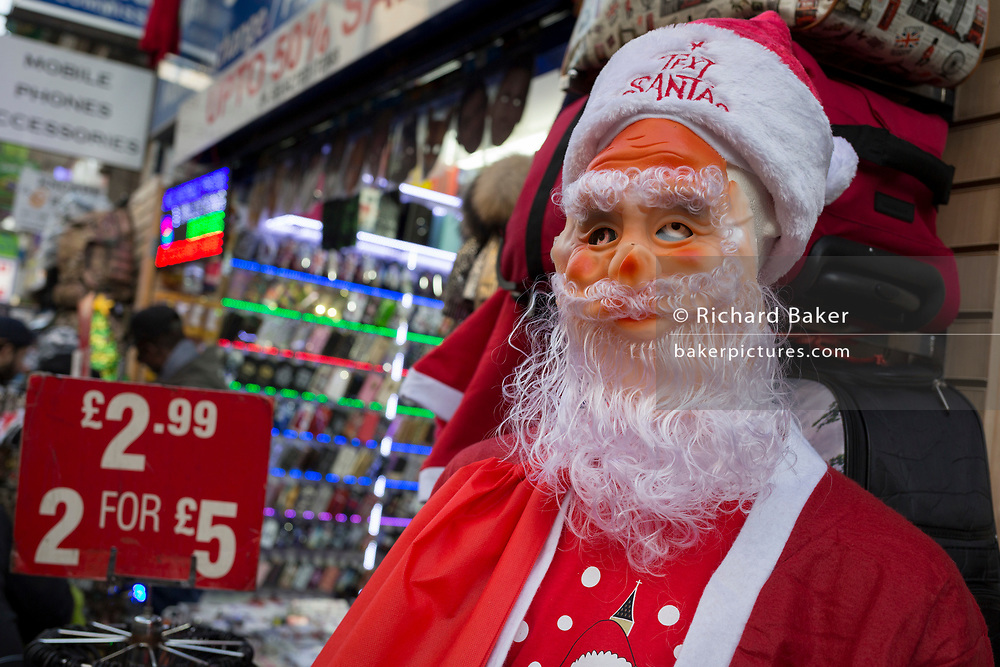 The scary eyes of a santa peers through the mask as it stands outside a budget shop selling trinkets on Oxford Street, on 12th December 2017, in London England.
