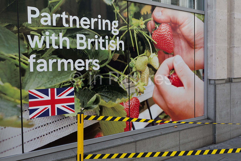 As Britain looks ahead to the possibility of a controversial No-Deal Brexit, and behnd hazard tape, a Tesco supermarket poster advertises the merits of British Farming and UK agriculture with a pair of hands picking fresh strawberries, on Cheapside in the City of London, the capitals financial district - aka the Square Mile, on 8th August, in London, England.