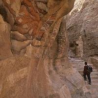 Hikers climb past colorful, layered sandstone on ancient up Umm Al-Bivara above Petra, Jordan.
