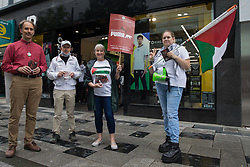 Slough, UK. 10th July, 2021. Pro-Palestinian activists canvass support from the public outside a branch of JD Sports during a Boycott Puma day of action. The nationwide day of action was organised by Palestine Solidarity Campaign in protest against Puma's sponsorship of the Israeli Football Association, which includes clubs playing in Israeli settlements in the occupied West Bank, and in response to a call from Palestinians to mark the 16th birthday this week of the Boycott, Divestment and Sanctions (BDS) movement.
