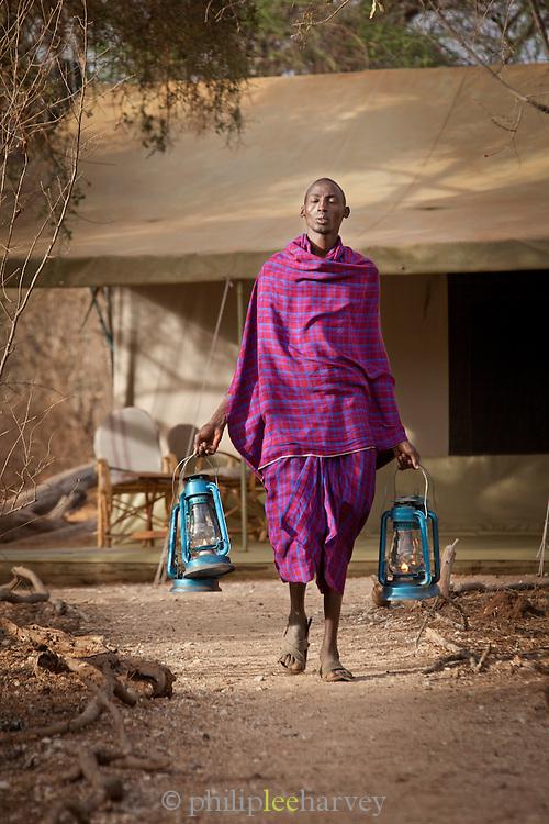 A maasai prepares a luxury camp for nightfall, in the Selenkay Reserve near Amboseli National Park, Kenya