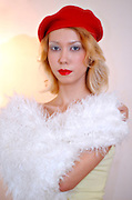 blond model in her 20s with white makeup red lips, white fur and red beret imitating christmas colours