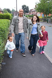 Young family walking down the street together,