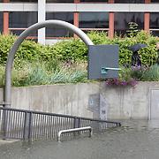 Foto: David Rozing Nederland Rotterdam 23 juni 2016  Wateroverlast. Door zware regenval staat waterplein Benthemplein helemaal vol: het eerste grootschalige waterplein. Rotterdam heeft het eerste grote waterplein van de wereld. Het waterplein wordt door de curves welvingen ook gebruikt om te skaten, door skaters. Een mooi plein midden in de stad, dat helpt om droge voeten te houden. Bij droog weer zijn er mooie plekken om te basketballen en te skaten, bij zware regenval kunnen de bassins het regenwater van het plein en de daken opvangen. Bij elkaar ongeveer 1,7 miljoen liter water. Dat water hoeft daardoor niet meer naar het riool, dat dus minder snel zal overstromen. En zo helpt het plein om droge voeten te houden terwijl regenbuien steeds heftiger worden. Een aantal studenten van scholen uit de buurt hebben bij de gemeente Rotterdam gevraagd of het mogelijk was het plein aan te passen. Dit paste uitstekend bij de wens van de gemeente en het Hoogheemraadschap van Schieland en de Krimpenerwaard om in de buurt een waterplein aan te leggen. plein in de weekenden gebruikt door skaters en bootcampers. Rotterdamse innovatie. Zoals veel steden, is Rotterdam dicht bebouwd. De stad heeft veel gebouwen en nog veel meer bestrating. Tegelijk worden regenbuien steeds heftiger, waardoor de kans op wateroverlast in de stad toeneemt. In Rotterdam zijn weinig mogelijkheden om extra ruimte te maken voor water, zoals singels, met name in de binnenstad. Zo ontstond in 2005 het idee van het waterplein: een plein dat bij droog weer een aantrekkelijke, leuke omgeving biedt, en dat er bij heftige regenbuien voor zorgt dat er minder water naar het riool en de singels stroomt. Op het Benthemplein worden alle principes van het waterplein toegepast De riolering is aangepast om de werking te optimaliseren. Foto: David Rozing