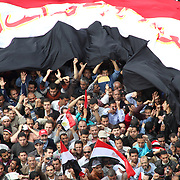 Hundreds of Egyptians hold an enormous national flag over their heads in Cairo's Tahrir Square.