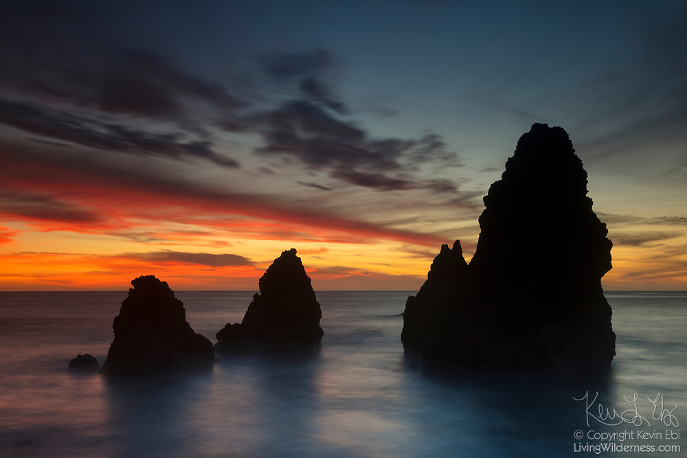 A dramatic sunset colors the sky behind large sea stacks in Rodeo Cove located in the Marin Headlands near San Francisco, California. The Marin Headlands are part of the Golden Gate National Recreation Area.