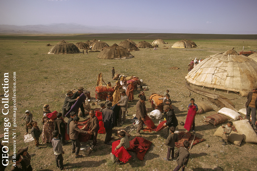 Shahsavan tribespeople pack their possessions in preparation for a move to summ er pastures. In the background can be seen some of their tent-like dwellings.