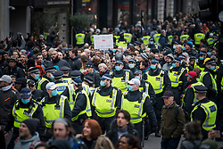 © Licensed to London News Pictures. 20/03/2021. London, UK. A heavy police presence watches over thousands of protesters as they gather on Piccadilly, during a Rally for Freedom in central London, to protest against the continued lockdown restrictions imposed to fight the spread of coronavirus. Similar events are taking place at cities around the world. Photo credit: Ben Cawthra/LNP