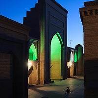Khiva is a World Heritage site along the Silk Road in Uzbekistan. A boy watches his friends play soccer at night. The players disappear because of the long camera exposure.