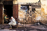 A metalsmith hammers out bent rebar and scraps for reuse at his street-side shop in Meknes, Morocco on November 1, 2007.