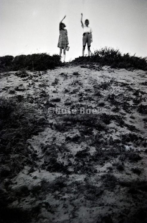 two children standing on top of a dune and waving 1950s Netherlands