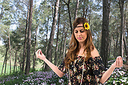 Teen Hippie girl meditates outdoors in a forest