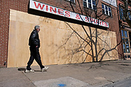 A man walks on Northampton Street past a boarded up Fine Wine & Good Spirits on Mar. 21, 2020, in Easton, Pennsylvania. Communities across the Lehigh Valley are adjusting to life during the coronavirus pandemic that is impacting the daily lives of Pennsylvania residents both socially and economically. (Photo by Matt Smith)
