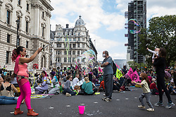 A woman creates bubbles as climate activists from Extinction Rebellion occupy roads around Parliament Square during a Back The Bill rally on 1st September 2020 in London, United Kingdom. Extinction Rebellion activists are attending a series of September Rebellion protests around the UK to call on politicians to back the Climate and Ecological Emergency Bill (CEE Bill) which requires, among other measures, a serious plan to deal with the UK's share of emissions and to halt critical rises in global temperatures and for ordinary people to be involved in future environmental planning by means of a Citizens' Assembly.