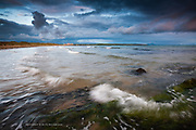 Waves wash over the reef at the long sandy Broad Beach, Rhosneigr, Anglesey during changeable and dramatic weather.
