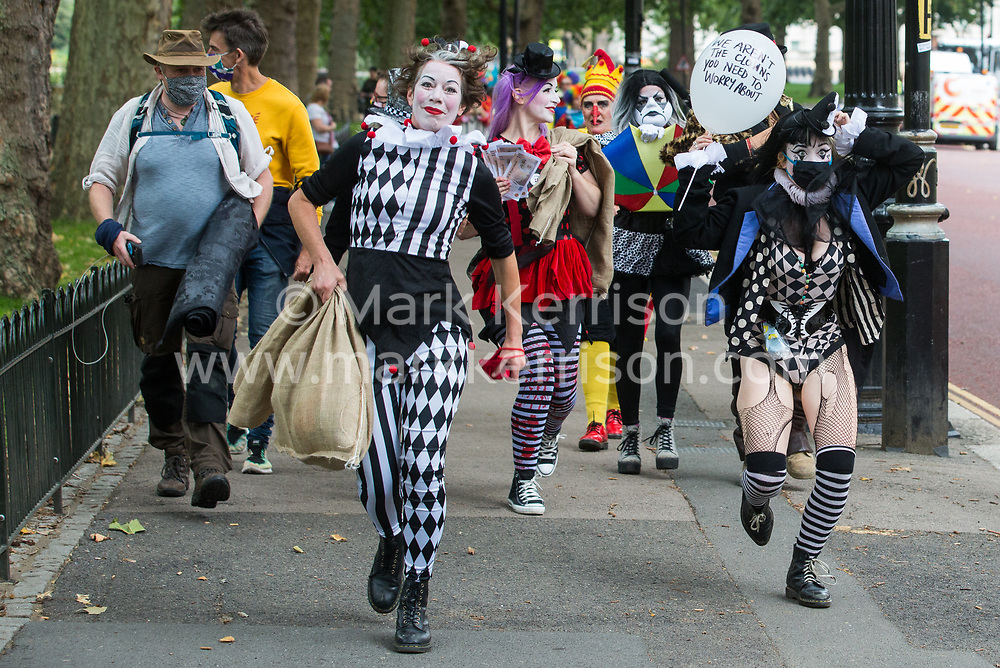 London, UK. 3rd September, 2020. A troupe of clowns joins fellow climate activists from Extinction Rebellion attending a 'Carnival of Corruption' protest against the government's facilitation and funding of the fossil fuel industry. Extinction Rebellion activists are attending a series of September Rebellion protests around the UK to call on politicians to back the Climate and Ecological Emergency Bill (CEE Bill) which requires, among other measures, a serious plan to deal with the UK's share of emissions and to halt critical rises in global temperatures and for ordinary people to be involved in future environmental planning by means of a Citizens' Assembly.