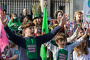 The SOS From The Kids Choir performs outside Buckingham Palace following a Rewild Royal Land procession organised by Wild Card, a new campaign calling on the UK's biggest landowners to rewild, and 38 Degrees on 9th October 2021 in London, United Kingdom. Campaigners including conservationist and broadcaster Chris Packham are calling on the Royal Family, the largest landowning family in the UK, to rewild their estates in order to assist with tackling the climate crisis and a 14-year-old boy presented a petition at the gates of Buckingham Palace signed by over 100,000 people.