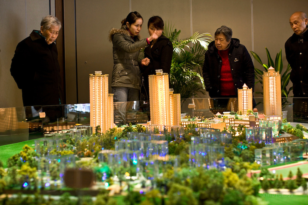 People look at a model of new apartment complex on sale Chana Colorful in Chongqing , China, March 3, 2009.