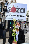 """London, United Kingdom, May 11, 2021: A Pro-Palestinian demonstrator holds a placard outside Downing Street to protest against Israeli air raids on Gaza Strip. Demonstrators chanted """"Free-Free Palestine!"""" demanding the commitment of Great Britain to end their support for Israel. (Photo by Vudi Xhymshiti/VXP)"""