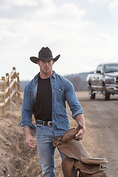 Rugged cowboy with a saddle in his hand walking on a dirt road on a ranch