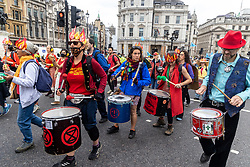 """Licensed to London News Pictures. 23/08/202. London, UK. Climate change protesters play the drums as Extinction Rebellion (XR), arrive in Trafalgar Square, London for the start of a 14 day protest with disruptive action and possible occupations of buildings and services. The protest, """"The Impossible Rebellion"""", want the government to implement their demand to stop all new fossil fuel investment immediately. Photo credit: Alex Lentati/LNP"""
