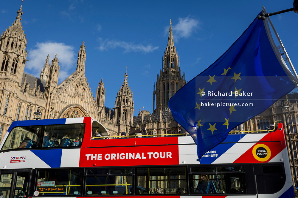 The stars of the EU flag fly over a London tour bus and the Houses of Parliament in Westminster, seat of government and power of the United Kingdom during Brexit negotiations with Brussels, on 23rd November 2017, in London England.