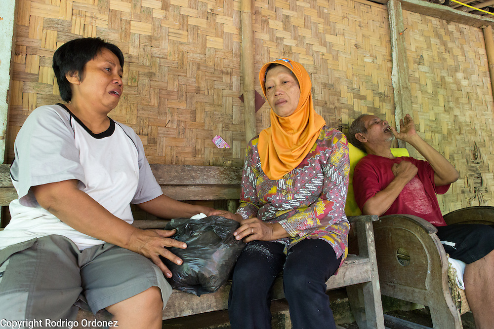 Community leader Suparjiyem, 49 (left), gets emotional while giving money and other items to Sumikem, 59 (center), a member of farmer's cooperative Menur, in Wareng, Wonosari subdistrict, Gunung Kidul district, Yogyakarta Special Region, Indonesia. Sumikem's husband Rajiman, 63 (right), had a stroke seven years ago.