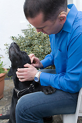 Man with a hearing impairment stroking his pet dog,