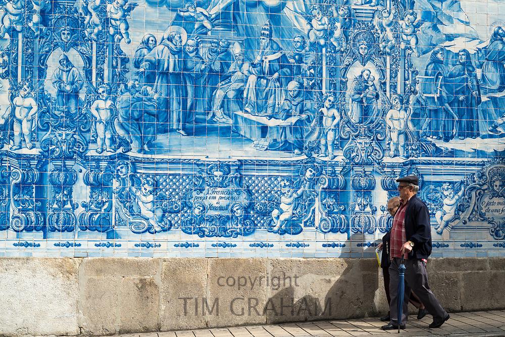 People passing Azulejos Portuguese blue and white wall tiles of Capela das Almas de Santa Catarina  - St Catherine's Chapel in Porto, Portugal