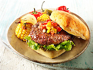 BBQ beef burger in a chabatta roll with salsa & BBQ vegetables on a rustic plate photos. Funky Stock Photos