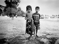 Children pause while playing in a squalid portion of the Tonle Sap village of Chong Kneas, Cambodia.